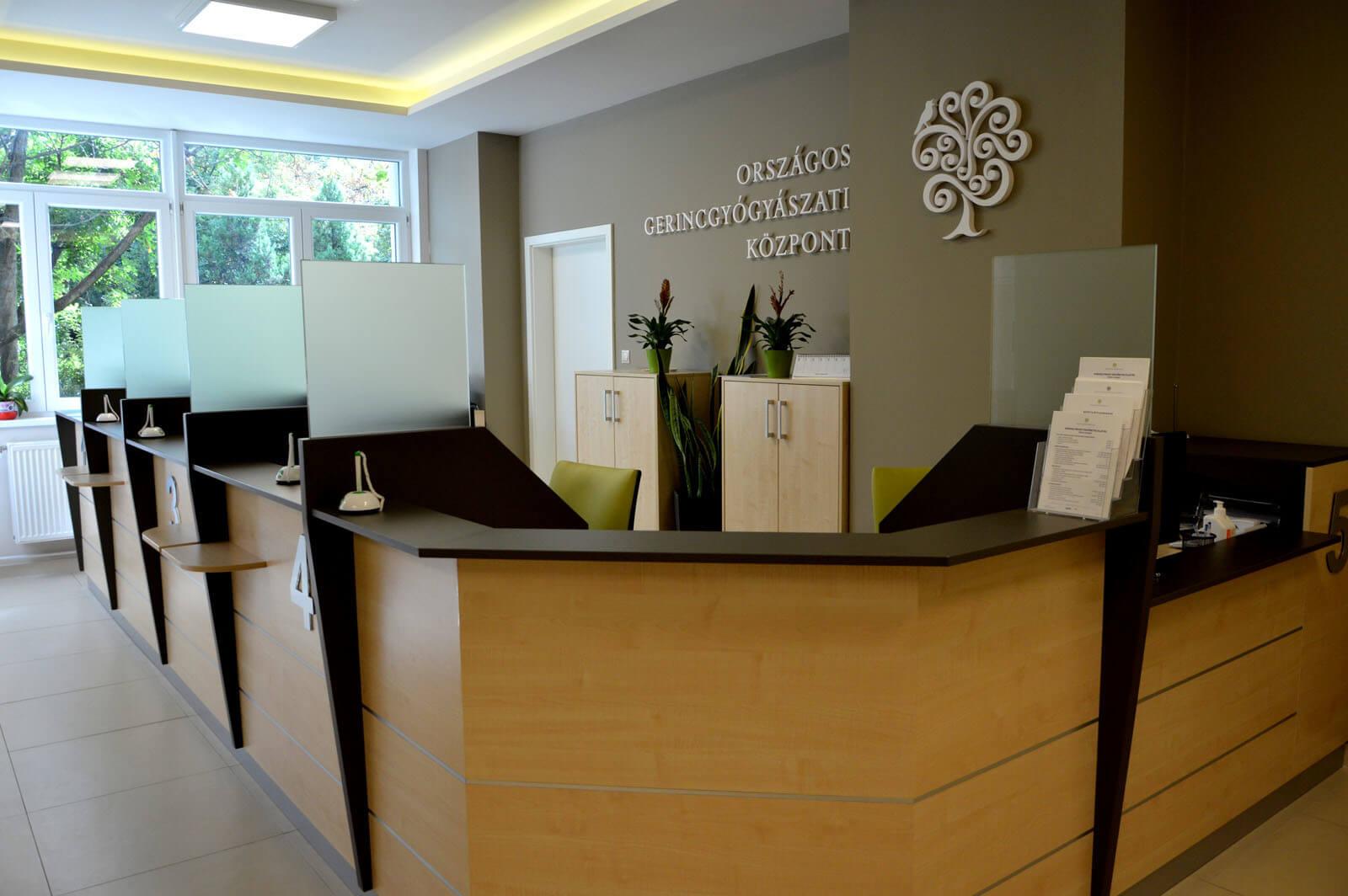 Egyedi recepciós pult készítés juhar színben, üveg elválasztóval, döntött előlappal, cégek részére