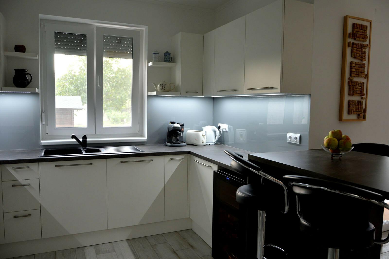 Modern - egyedi konyhabútor fehér - szürke színben, üveghátlappal, rejtett LED világítással, beépített borhűtővel, szigetrésszel