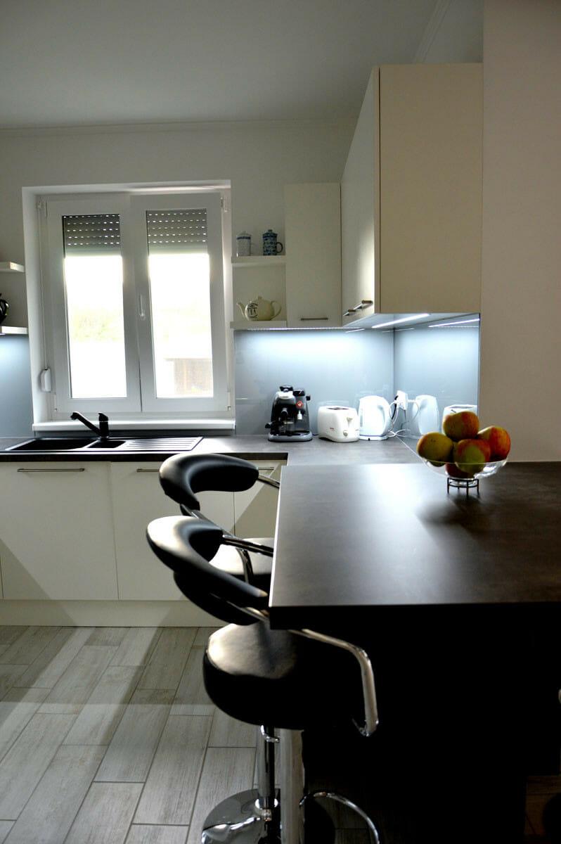 Modern - egyedi konyhabútor fehér - szürke színben, üveghátlappal, rejtett LED világítással, beépített borhűtővel