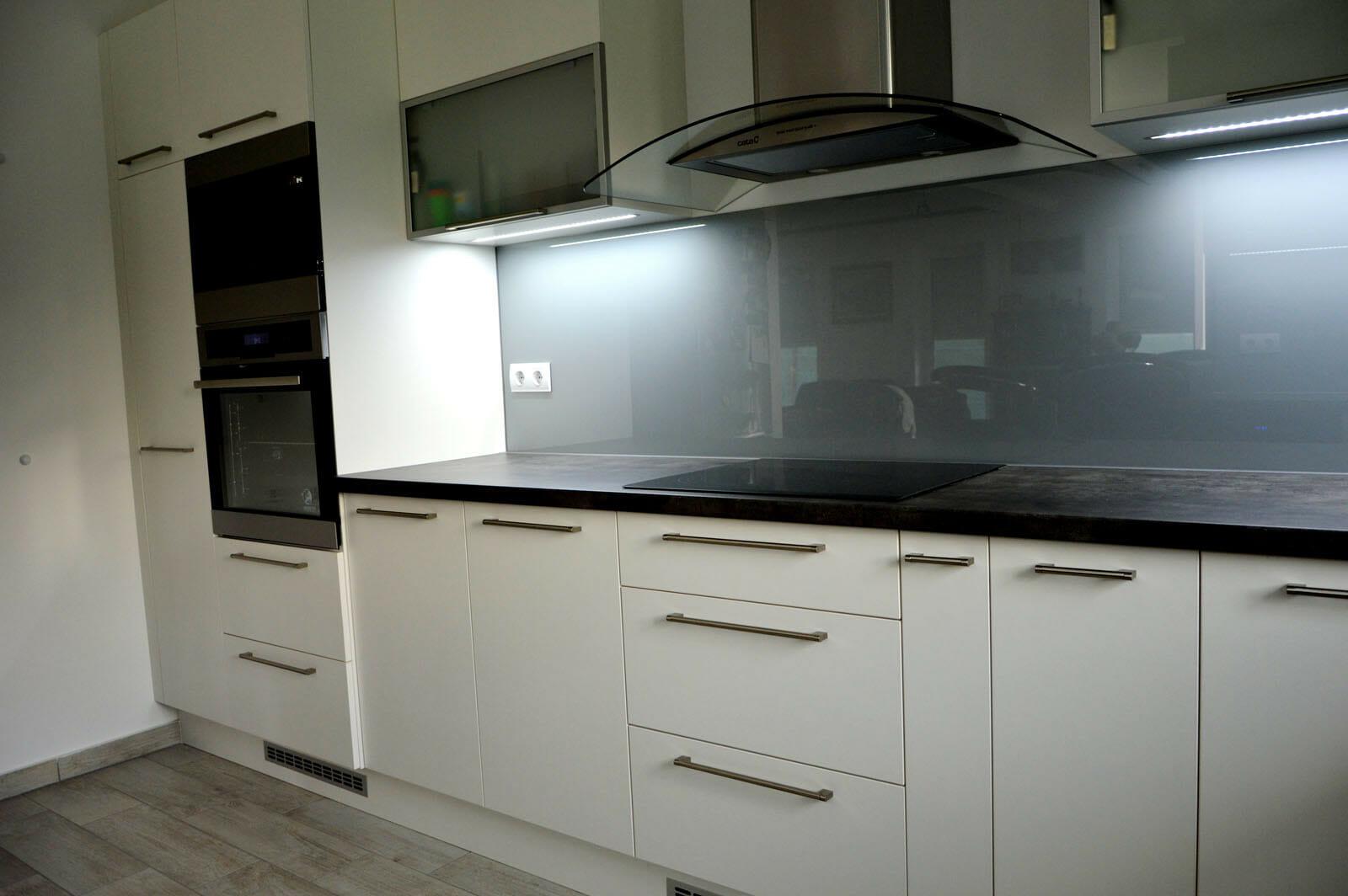 Modern - egyedi konyhabútor fehér - szürke színben, üveghátlappal, rejtett LED világítással, beépített konyhai gépekkel