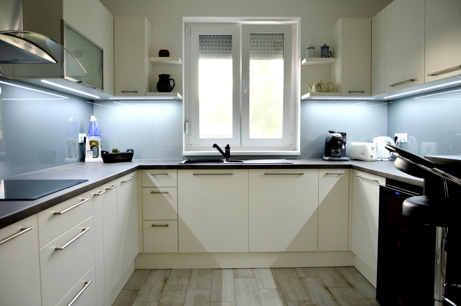 Modern - egyedi konyhabútor fehér - szürke színben, üveghátlappal, rejtett LED világítással, beépített mosogatógéppel, blum aventos HF felnyíló vasalattal