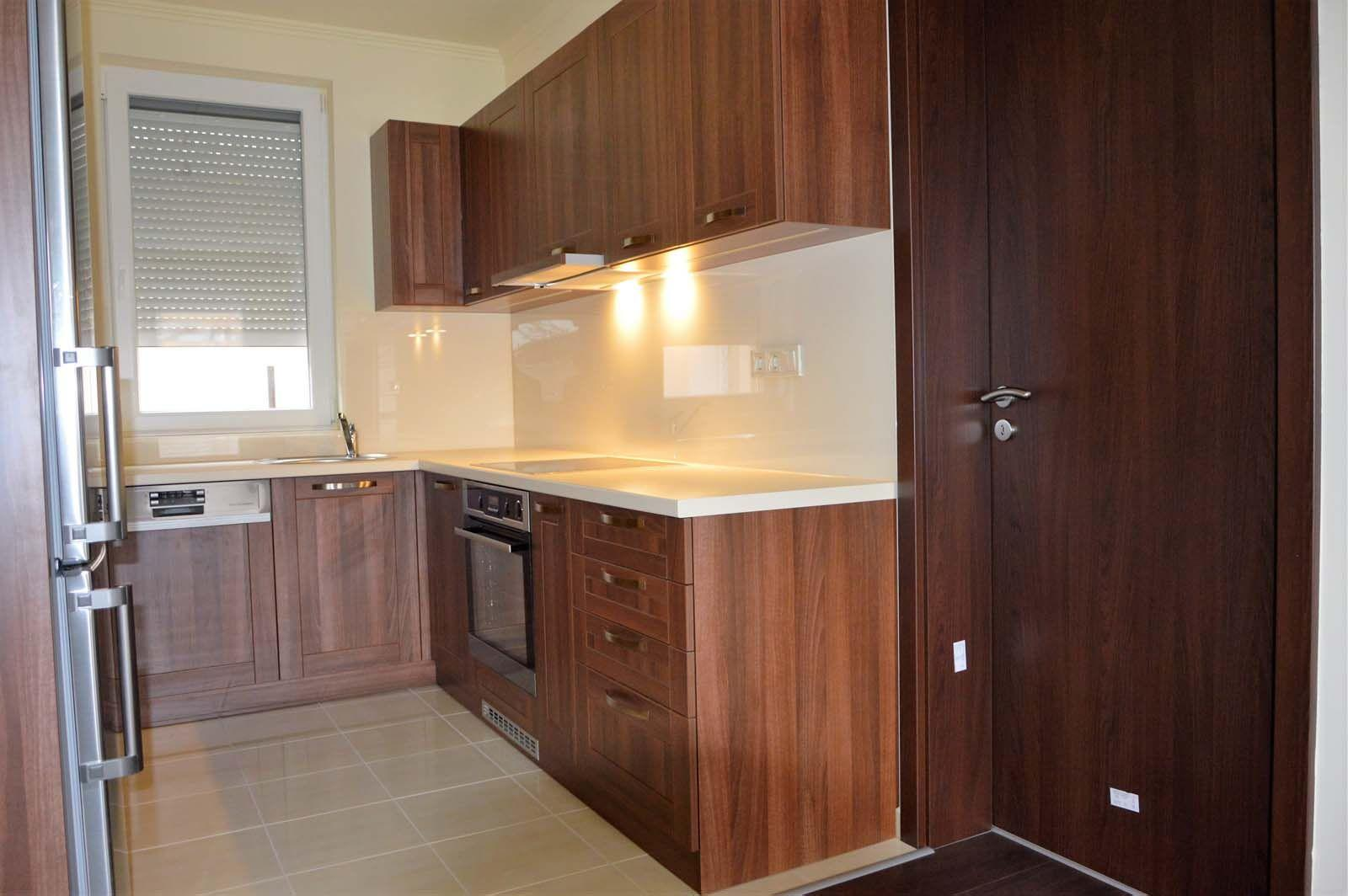 Egyedi konyhabútor készítés dió - bézs színben üveghátlappal, rejtett LED világítással, beépített konyhai gépekkel