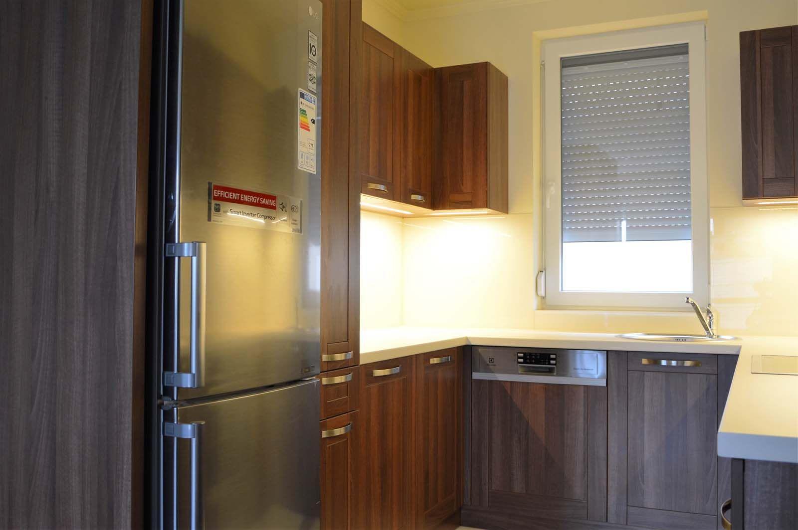 Egyedi konyhabútor készítés dió - bézs színben üveghátlappal, rejtett LED világítással, hűtő takarással