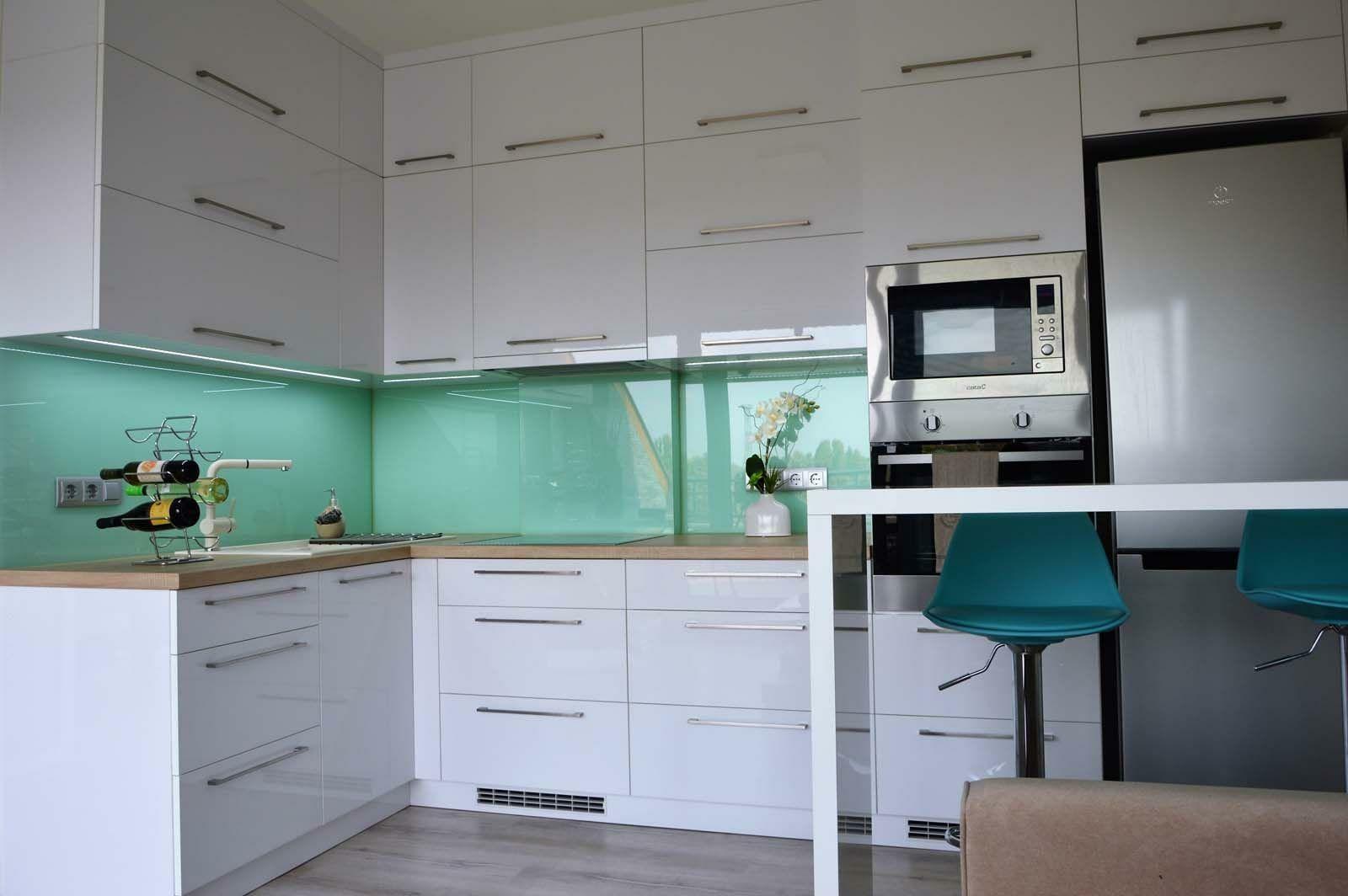 Egyedi konyhabútor készítés magasfényű akril felületű bútorlapból üveghátlappal, rejtett LED világítással, étkező pulttal