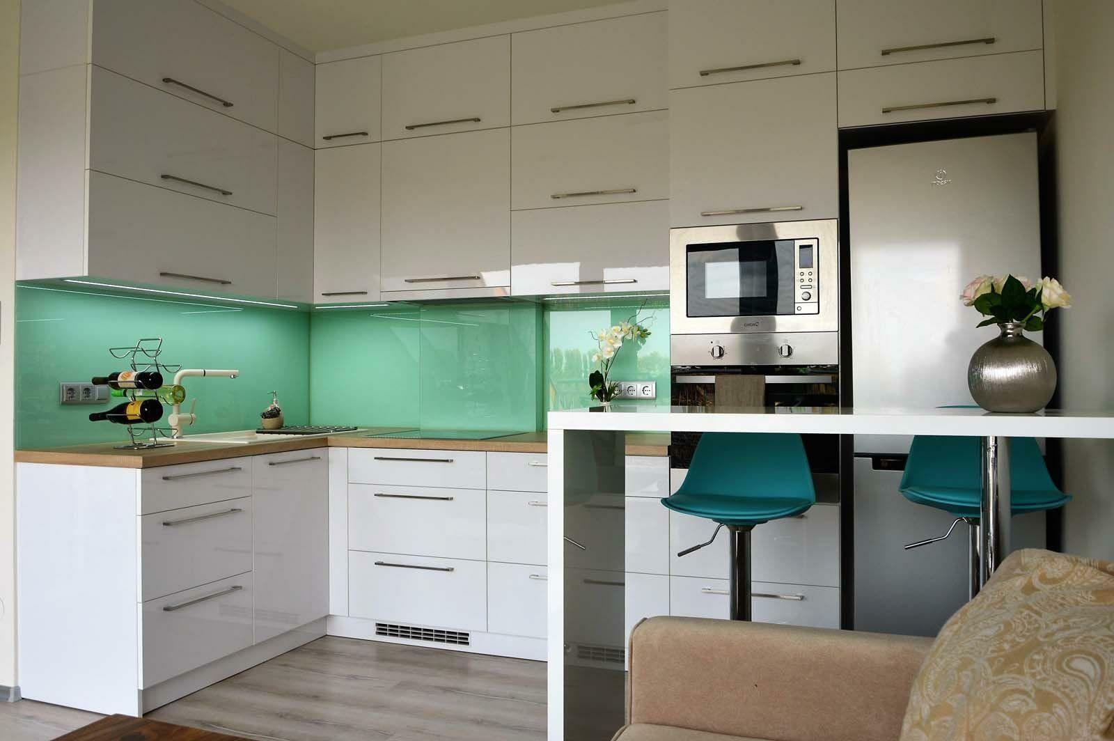 Egyedi konyhabútor készítés magasfényű akril felületű bútorlapból üveghátlappal, rejtett LED világítással, minden rendelkezésre álló hely kihasználásával