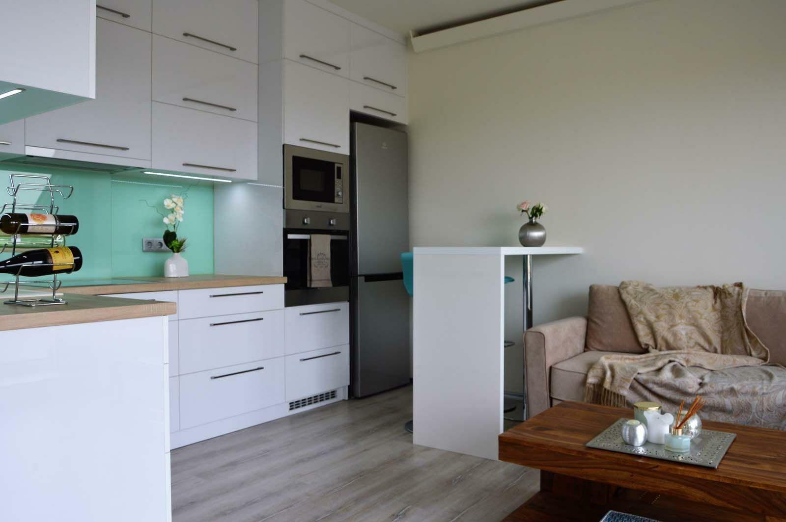 Egyedi konyhabútor készítés magasfényű fehér akril felületű bútorlapból üveghátlappal, rejtett LED világítással