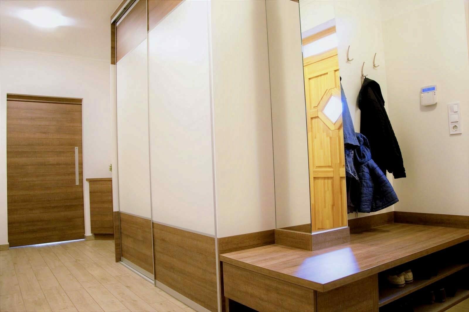 Egyedi előszoba bútor tolóajtós beépített szekrénnyel, nyitott polcos cipősrésszel, fali akasztós elemekkel, tükörrel, színbe megeggyező térelválasztó tolóajtós, duplungolt ülöfelülettel
